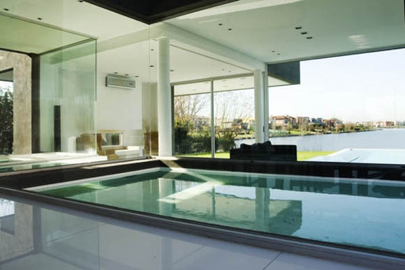 <br>Both programs are connected by a glass bridge, with the water running under your feet. The living room, 10 meters wide and 5 meters length, opens to the exterior using glass walls. It was thought in a lower level than the rest of the house, making it permeable and allowing the ambients a clean view to the lake.<br><br>