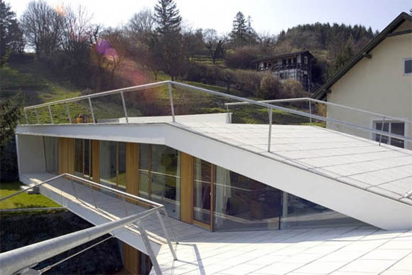 <br>Реализация<br><br>«Складывающийся» дом состоит из двух частей. Ломаные линии создают впечатление об организации большого пространства. Здание позволяет жильцам наслаждаться пейзажем благодаря большим окнам на южном фасаде. Особую роль для создания эффекта пространства играет белый цвет. Ограждающая стена на северной стороне завершает изгиб комнаты. Вертикальная планировка реализована как освещенная ниша на протяжении всего здания, соединяющее обе его части. Ниша пропускает больше света в помещения благодаря доминирующему вертикальному дневному освещению, упрощает ориентацию.<br><br> <br>