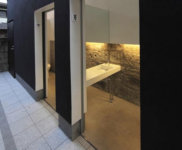 """Не смотря на маленькую площадь, ванные кажутся легкими и светлыми благодаря высоким потолкам с панорамным вторым светом. Уборные выгладят не только как путь к сохранению специфичного пейзажа региона, но и создают отправную точку для новой архитектуры города. <br>Наружные стены покрыты эластичной штукатуркой, в то время как внутренние стены выполнены в белом материале, известном как """"Shikkui"""", который используется при высокой влажности и отвечает противопожарным требованиям города."""